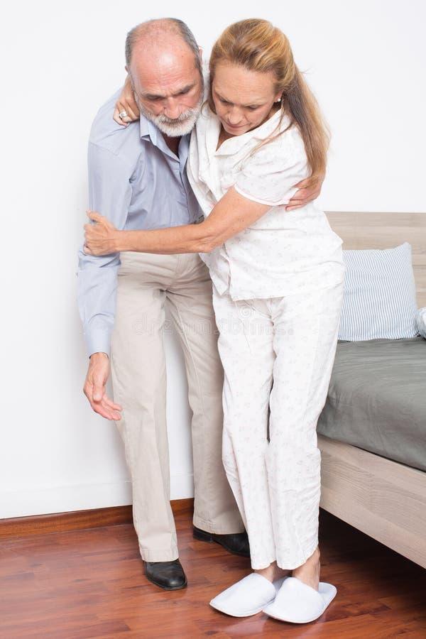 O marido ajuda a esposa a sair da cama imagem de stock royalty free