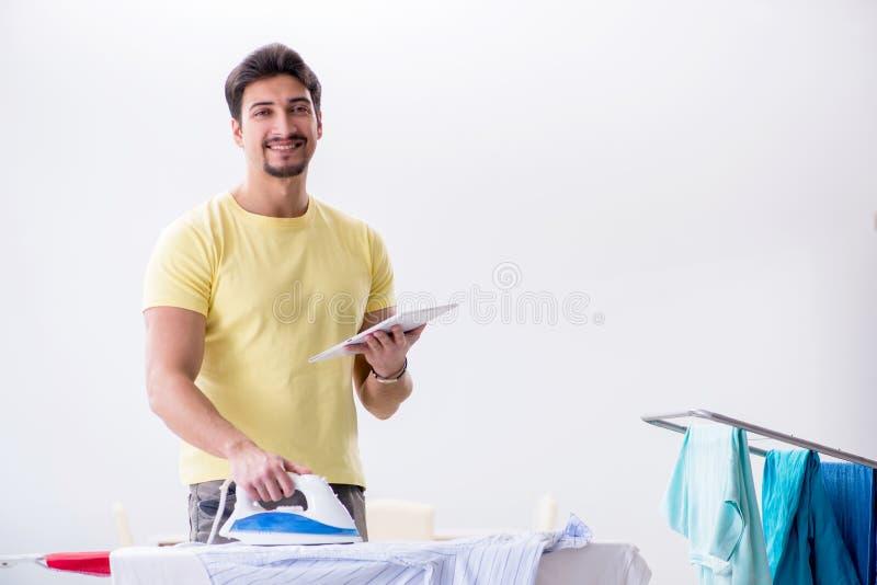 O marido considerável do homem que faz a roupa que passa em casa foto de stock royalty free
