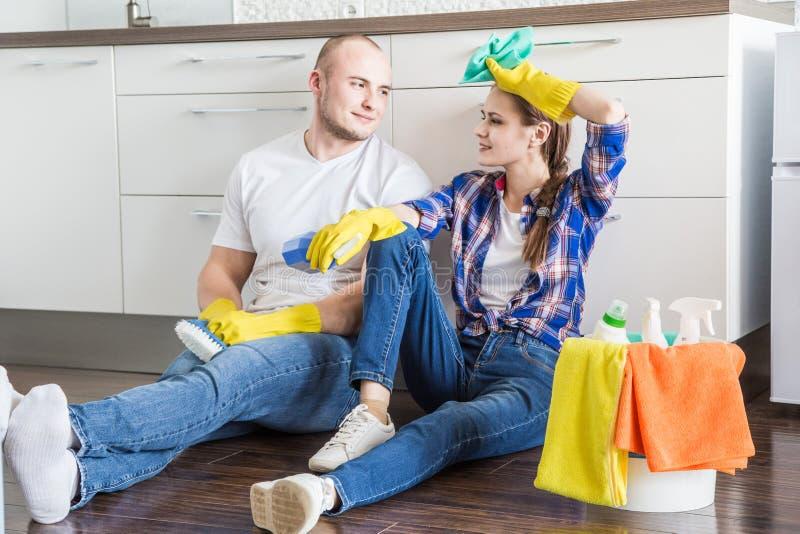 O marido e a esposa novos dos pares fazem a limpeza da casa O indiv?duo e a menina lavam a cozinha com um espanador e um pano fotos de stock