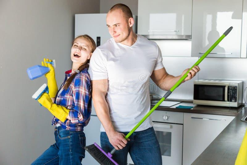 O marido e a esposa novos dos pares fazem a limpeza da casa O indiv?duo e a menina lavam a cozinha com um espanador e um pano imagens de stock