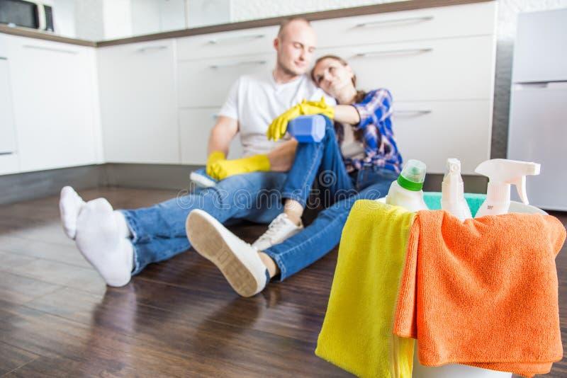 O marido e a esposa novos dos pares fazem a limpeza da casa O indiv?duo e a menina lavam a cozinha com um espanador e um pano foto de stock royalty free