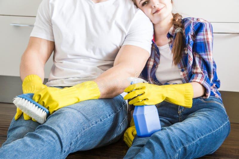 O marido e a esposa novos dos pares fazem a limpeza da casa O indiv?duo e a menina lavam a cozinha com um espanador e um pano fotografia de stock royalty free