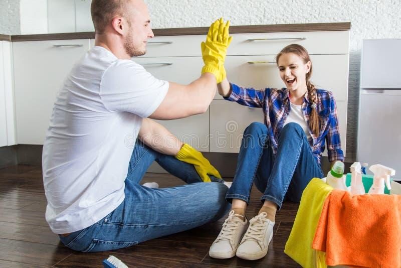 O marido e a esposa novos dos pares fazem a limpeza da casa O indiv?duo e a menina lavam a cozinha com um espanador e um pano foto de stock