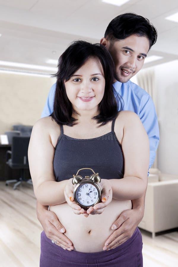O marido guarda a barriga grávida com pulso de disparo imagem de stock