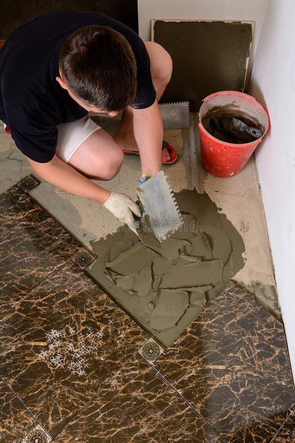 O marido mestre pressiona uma solução glutinosa da espátula à superfície do cimento imagem de stock