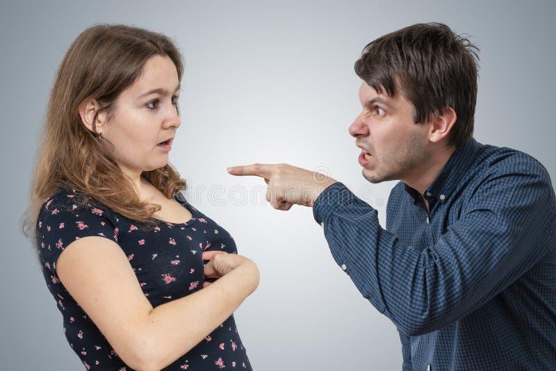O marido novo da inveja é gritaria e acusação de sua esposa imagens de stock