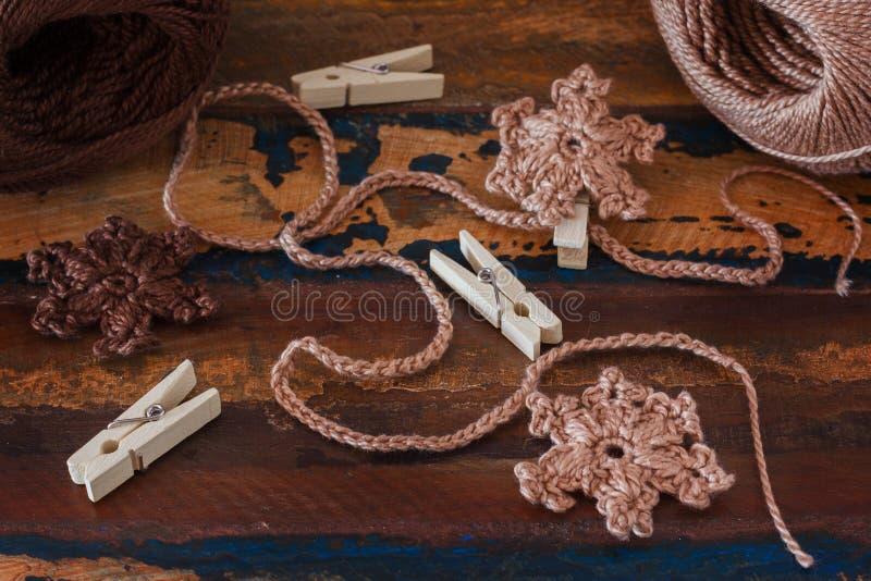O marrom feito a mão faz crochê flocos de neve para a decoração do Natal do ch fotografia de stock