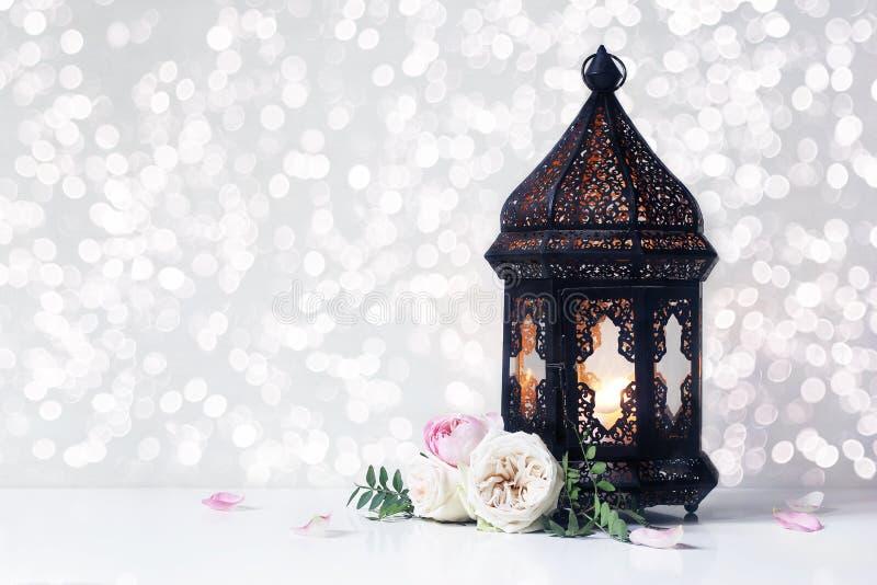 O marroquino preto do vintage, lanterna árabe com vela de incandescência, ramos verdes, aumentou flores e pétalas na tabela branc imagens de stock