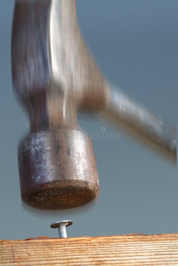 O martelo bate o prego na cabeça. fotografia de stock royalty free