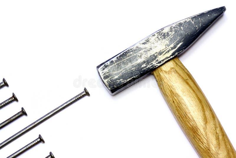 O martelo bate um prego imagens de stock royalty free