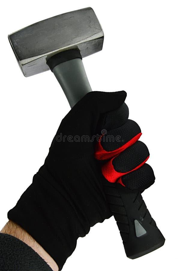 O martelo de aço dado forma quadrado pequeno realizou na mão esquerda na luva de nylon preta com esboço vermelho fino, fundo bran fotografia de stock royalty free