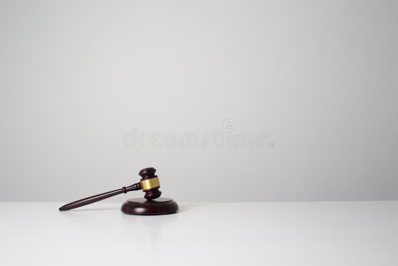 O martelo de madeira preto pôs sobre a tabela branca da mesa foto de stock royalty free