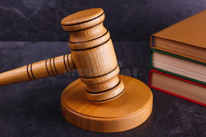 O martelo do juiz está no suporte ao lado de uma pilha do close-up dos livros em um fundo de pedra Vista lateral imagens de stock royalty free