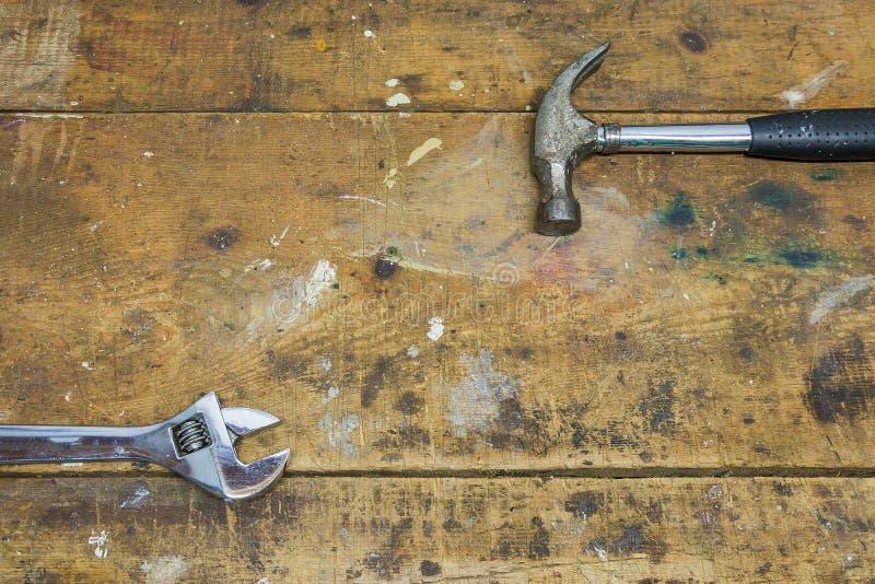 O martelo e a chave na oficina do trabalho bench o fundo foto de stock royalty free