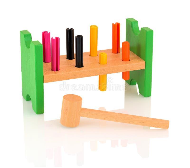 O martelo e o prego de madeira brincam para as crianças isoladas no fundo branco com reflexão da sombra fotografia de stock