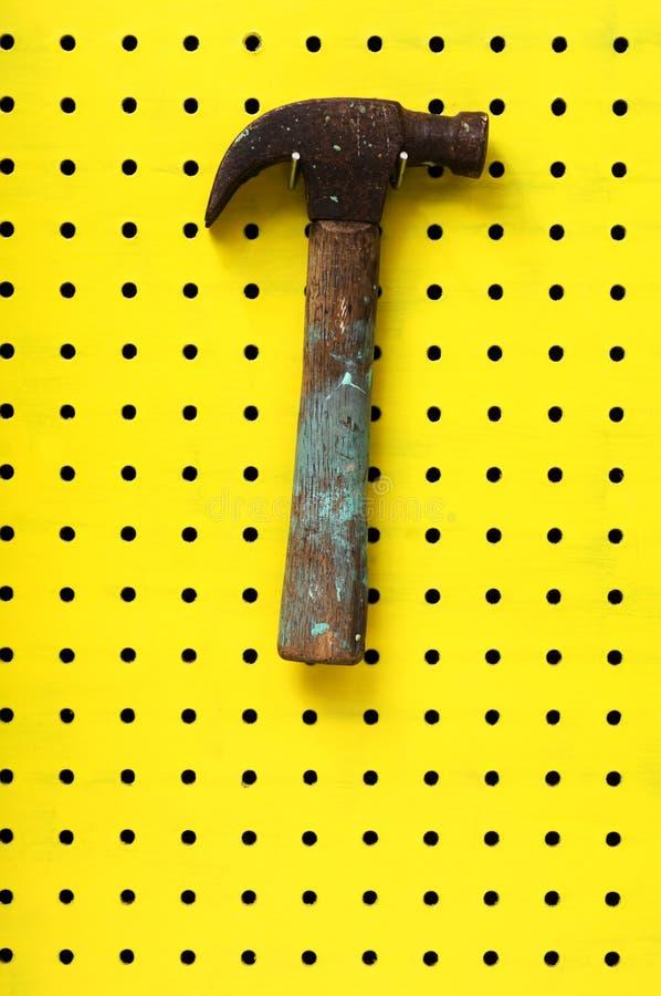 O martelo pendura em dois ganchos da placa de Peg amarela foto de stock royalty free