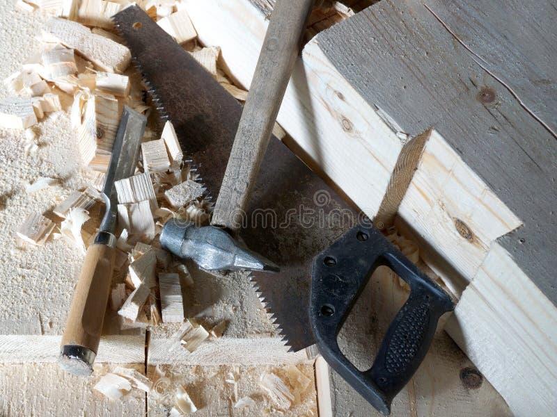 O martelo, a serra e o form?o est?o nas placas imagens de stock