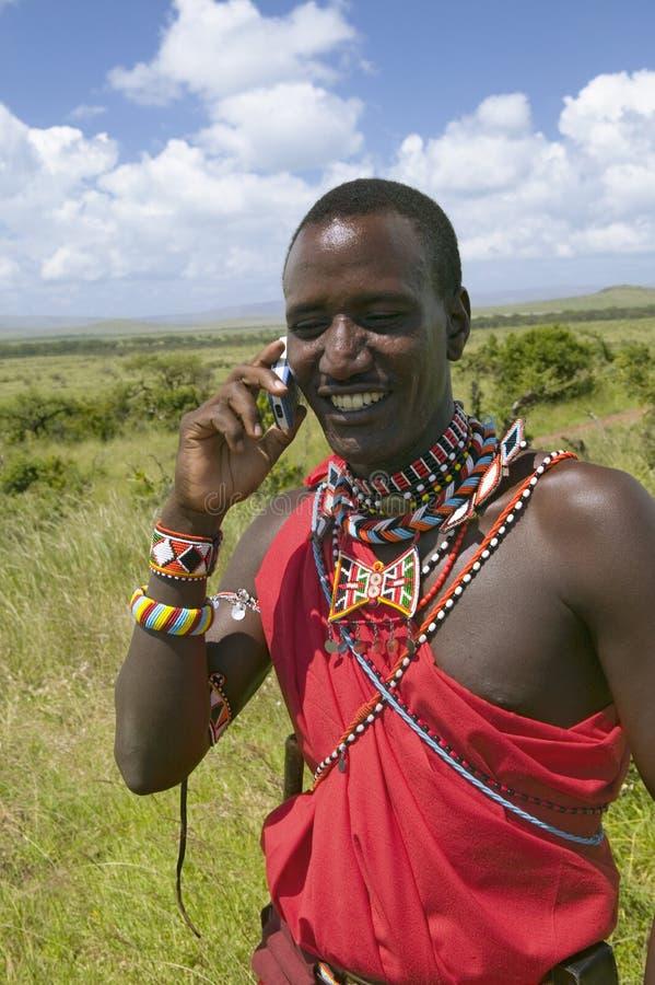 O Masai na toga vermelha fala em seu telefone celular das pastagem da tutela dos animais selvagens de Lewa em Kenya norte, África imagens de stock