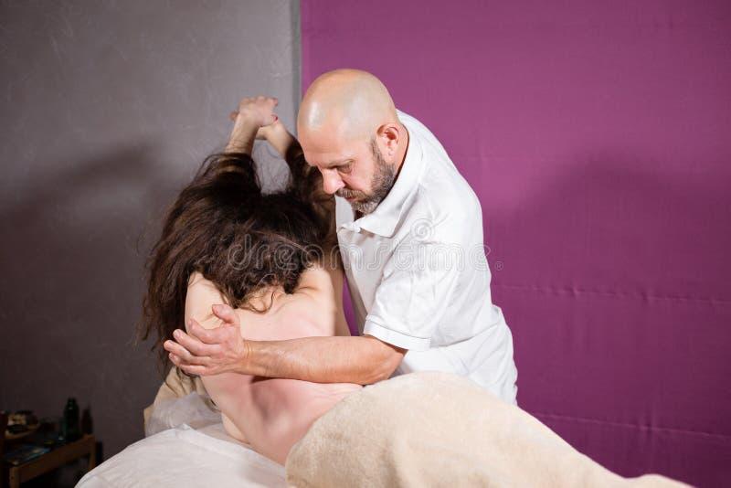 O massagista entrega fazer a espinha e massagem traseira, pescoço e mão O paciente relaxado aprecia Mãos do homem que fazem massa fotos de stock royalty free