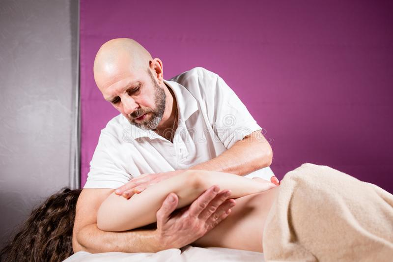 O massagista entrega fazer a espinha e massagem traseira, pescoço e mão O paciente relaxado aprecia Mãos do homem que fazem massa fotografia de stock