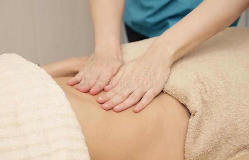 O massagista faz a massagem da cura do abdômen para uma mulher foto de stock