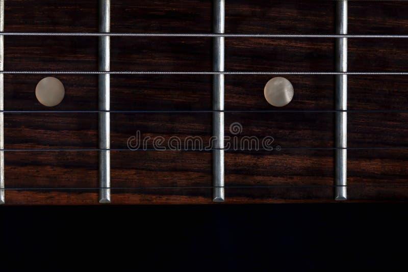 O mastro com as fricções de uma guitarra elétrica no fundo preto imagem de stock