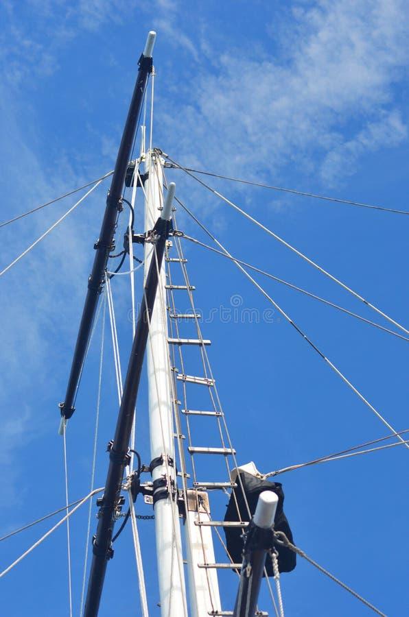 O mastro de um iate que aumenta contra um céu azul imagem de stock