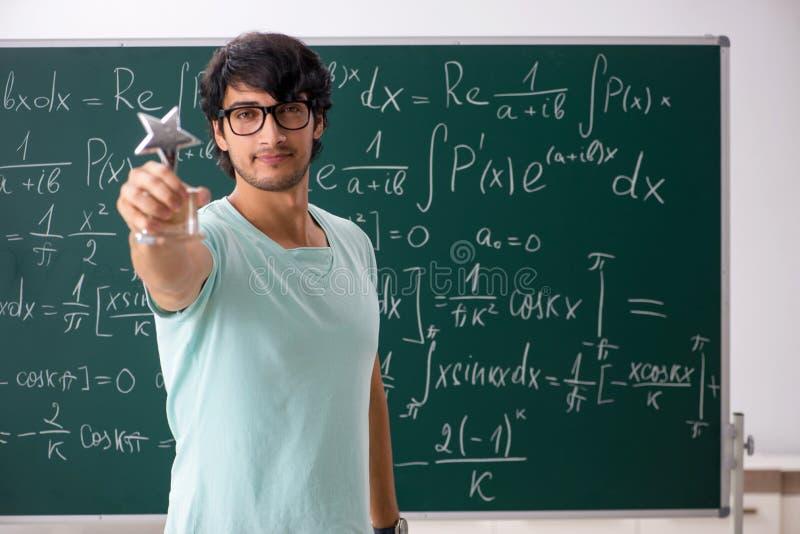 O matemático novo do estudante masculino na frente do quadro foto de stock