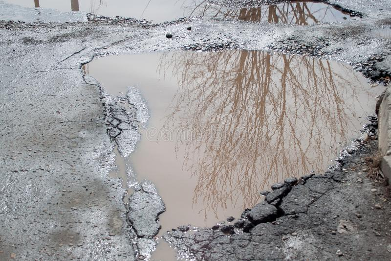 O mau asfaltou a estrada rodoviária com um caldeirão grande enchido com água Roadbed destruído perigoso foto de stock royalty free