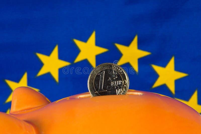 O mealheiro com a uma euro- moeda, UE embandeira no fundo foto de stock