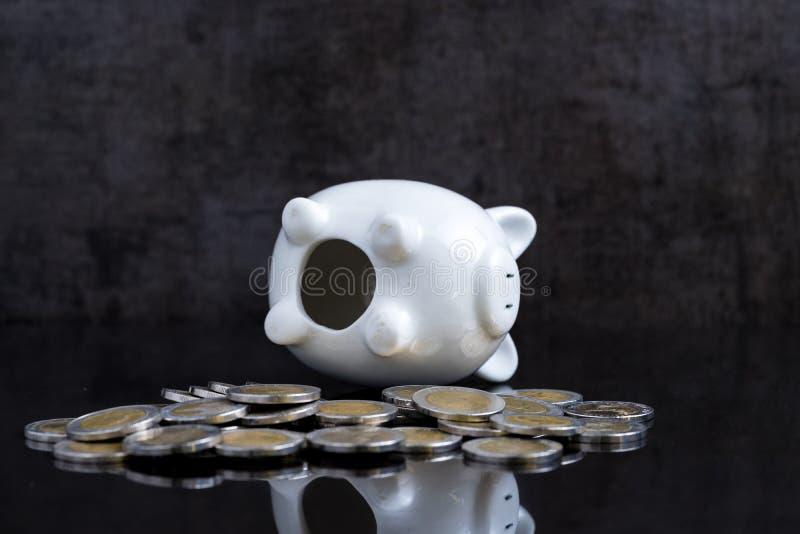 O mealheiro vazio coloca na tabela do preto escuro com moedas usando-se como o bro imagens de stock royalty free