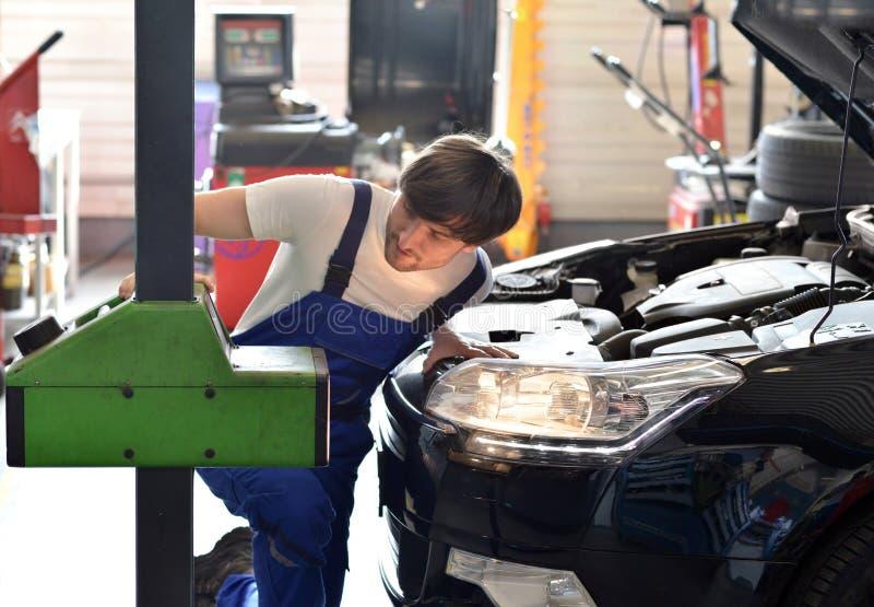 O mecânico ajusta faróis do carro em uma oficina imagem de stock royalty free