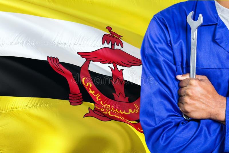 O mecânico Bruneian no uniforme azul está mantendo a chave contra a ondulação do fundo da bandeira de Brunei Darussalam Técnico c imagem de stock