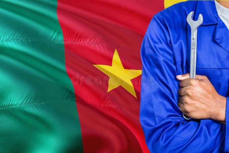 O mecânico camaronês no uniforme azul está mantendo a chave contra a ondulação do fundo da bandeira de República dos Camarões Téc fotos de stock royalty free