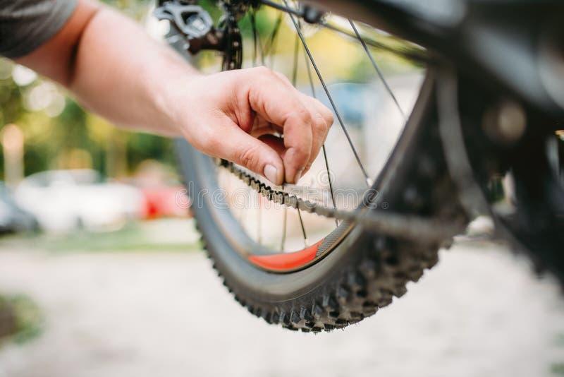 O mecânico da bicicleta no avental ajusta a corrente da bicicleta imagens de stock