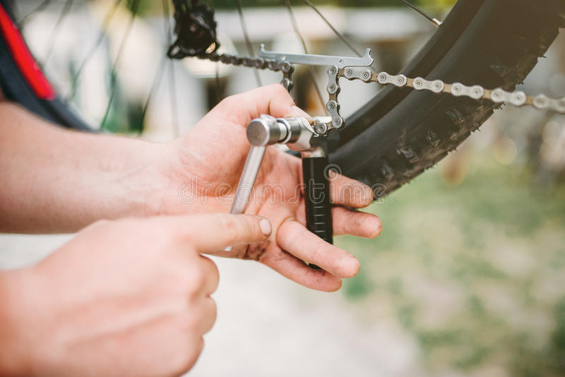 O mecânico da bicicleta no avental ajusta a corrente da bicicleta foto de stock
