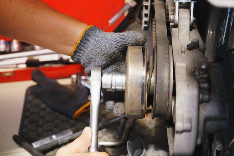 O mecânico da motocicleta que usa o soquete da chave de impacto substitui o sistema da embreagem no 'trotinette' grande na garage imagens de stock royalty free