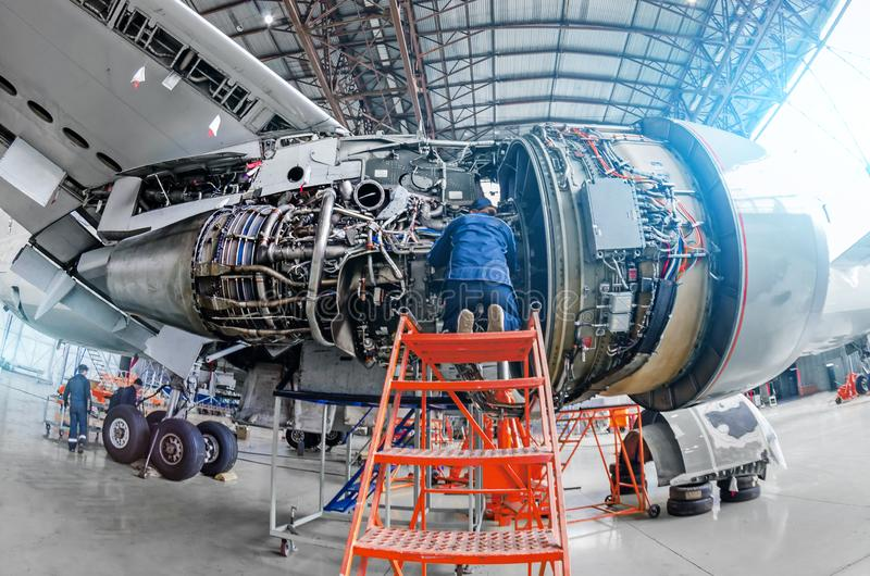 O mecânico de avião diagnostica o motor de jato dos reparos através do portal aberto fotografia de stock royalty free
