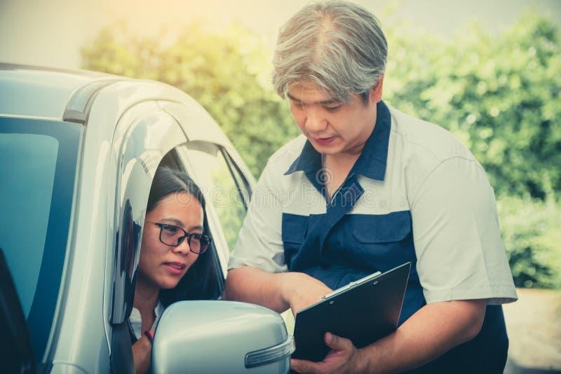 O mecânico de carro está descrevendo os detalhes da inspeção do carro Para as mulheres que possuem compreendendo antes de reparar imagem de stock royalty free