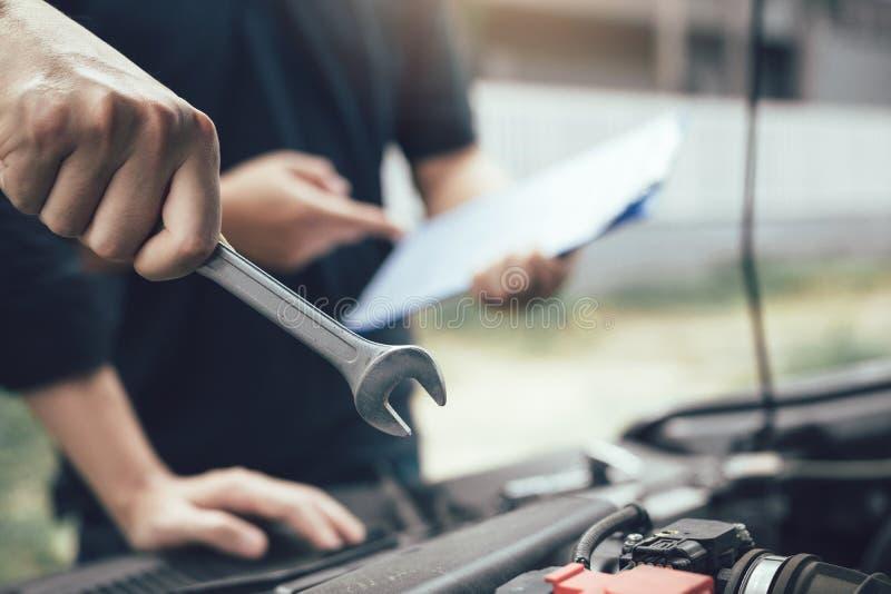 O mecânico de carro está mantendo uma chave pronta para verificar o motor e para mantê-lo com o assistente imagem de stock royalty free