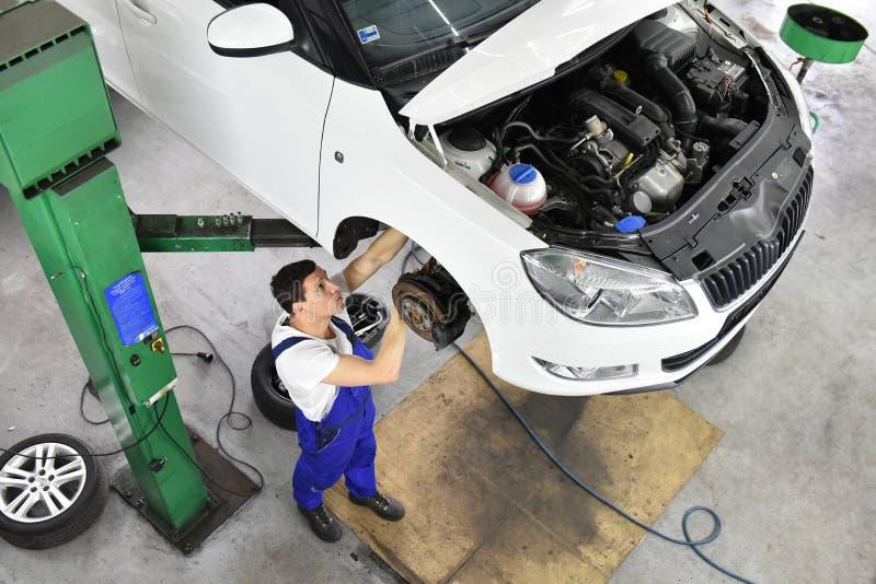 O mecânico de carro trabalha em uma oficina, reparo dos carros fotos de stock royalty free