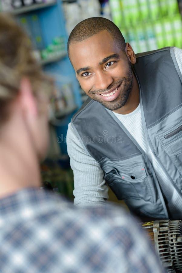 O mecânico de sorriso fala ao cliente sobre a peça do carro foto de stock