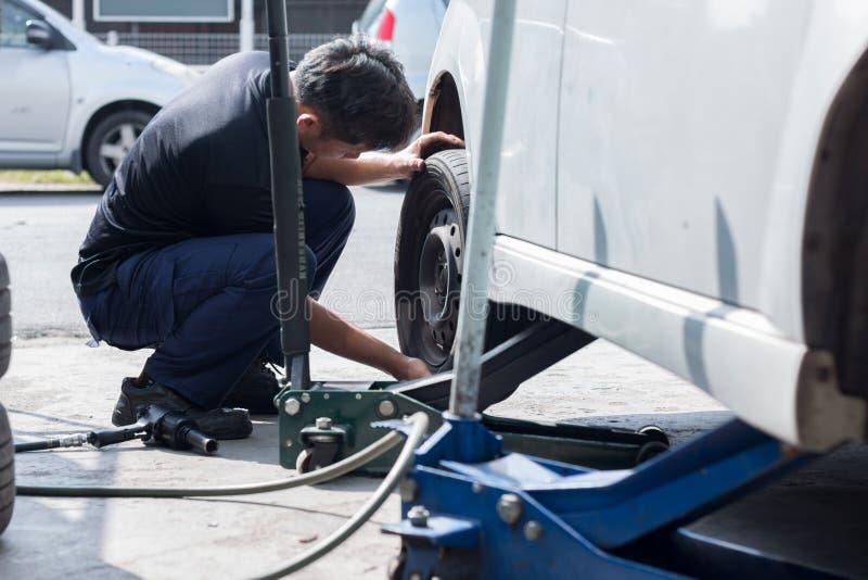 O mecânico está mudando a roda de carro na loja do pneumático imagens de stock royalty free