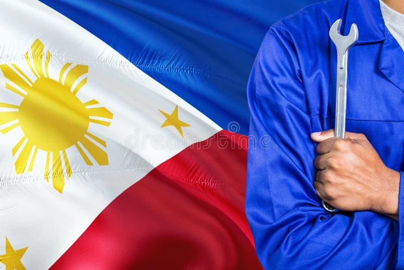 O mecânico filipino no uniforme azul está mantendo a chave contra a ondulação do fundo da bandeira de Filipinas Técnico cruzado d imagens de stock royalty free
