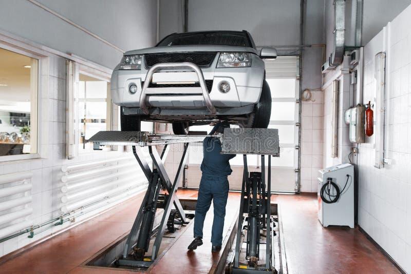 O mecânico inspeciona o sistema de suspensão de carro levantado imagens de stock