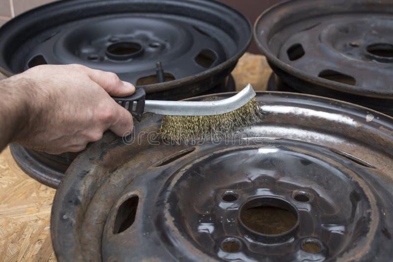 O mecânico limpa a borda de aço da roda manualmente com uma escova de fio imagens de stock royalty free
