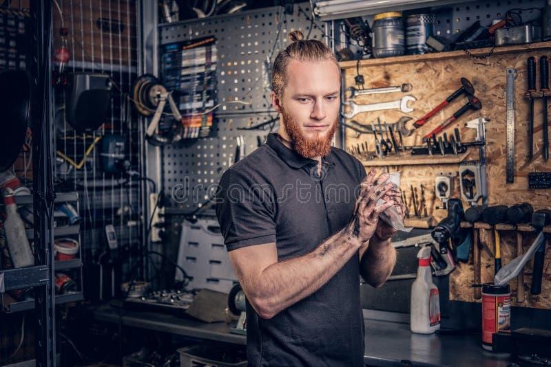O mecânico limpa seus braços após o manual do serviço da bicicleta imagem de stock royalty free