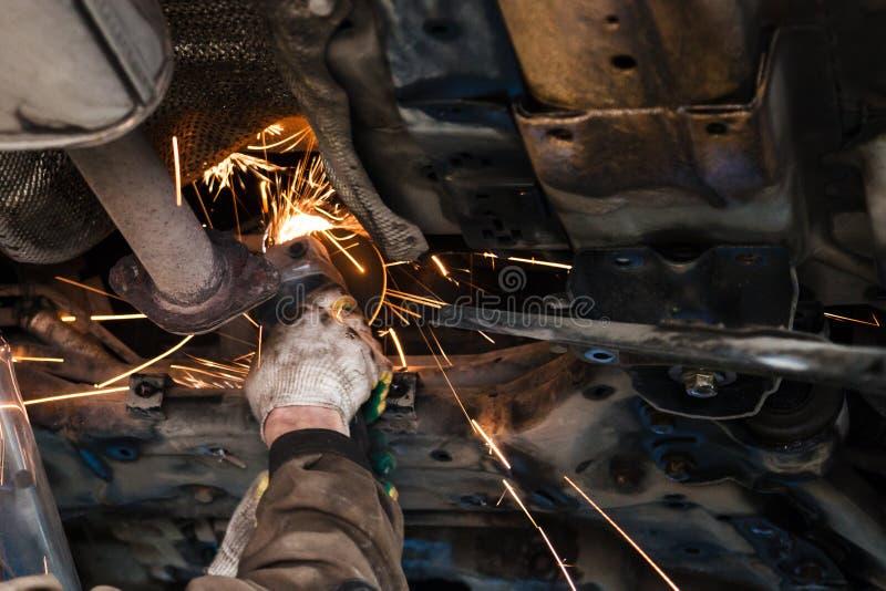 O mecânico limpa a tubulação do silenciador pelo moedor de ângulo imagem de stock royalty free