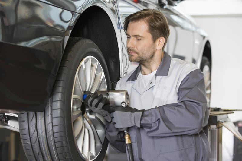 O mecânico masculino que repara o carro roda dentro a oficina foto de stock