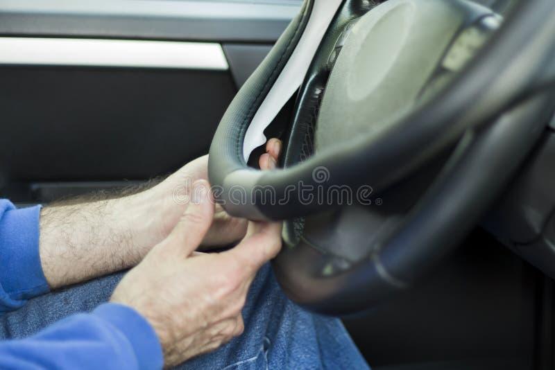 O mecânico põe a tampa do weel sobre o volante fotos de stock